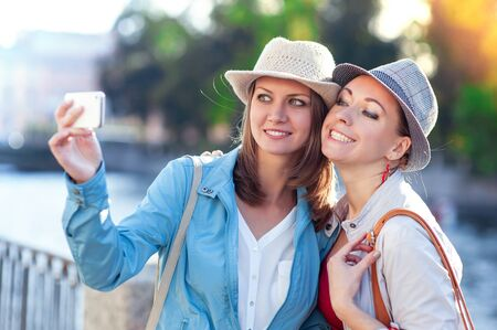 taken: Two happy beautiful girls taken picture of themself in the city outdoor Stock Photo