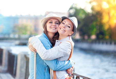 Two beautiful girls laughing and hug in the city outdoor