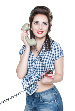 Young beautiful woman in pin-up style with retro telephone isolated over white photo