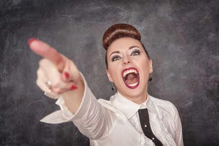 finger in mouth: Angry screaming woman in white blouse pointing out on the chalkboard background