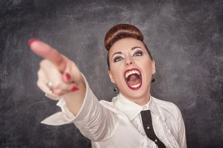 Boze gillende vrouw in witte blouse wijzen op het bord achtergrond Stockfoto