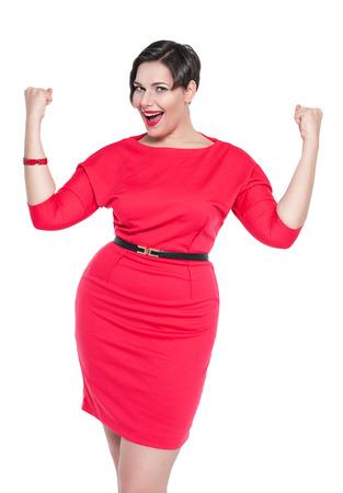 Mooie plus size vrouw in rode jurk met ja gebaar geïsoleerd op witte achtergrond