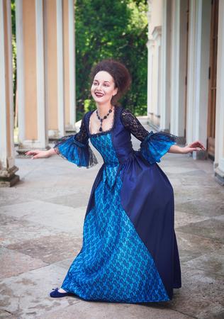 medieval dress: Joven y bella mujer en vestido medieval azul haciendo reverencia al aire libre