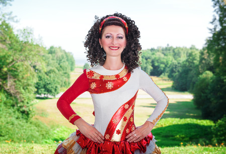 irish woman: Young woman in red and white irish dance dress and wig posing outdoor