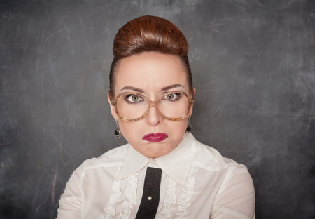 Angry teacher with eyeglasses on the school blackboard background Stock Photo