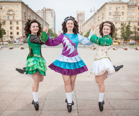 irish woman: Three women in irish dance dresses and wig posing outdoor Stock Photo