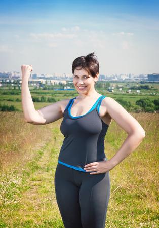 puños cerrados: Fitness hermosa talla grande mujer que muestra gesto afirmativo al aire libre