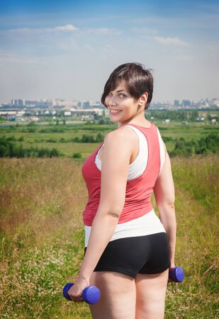 to size: Beautiful plus size woman exercising with dumbbells outdoor