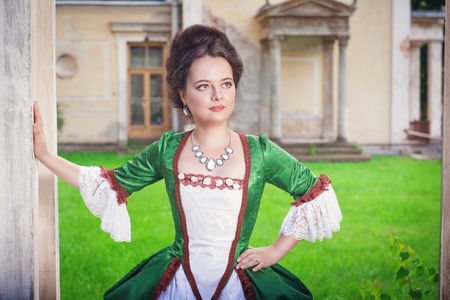 ruche: Beautiful young woman in green medieval dress outdoor