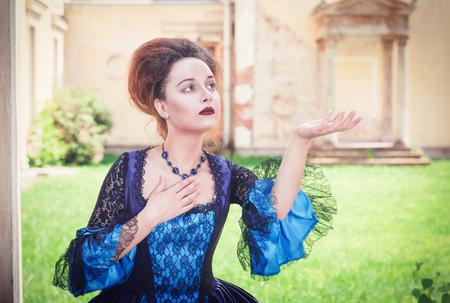 medieval dress: Joven y bella mujer en vestido medieval azul que estira la mano a algo exterior