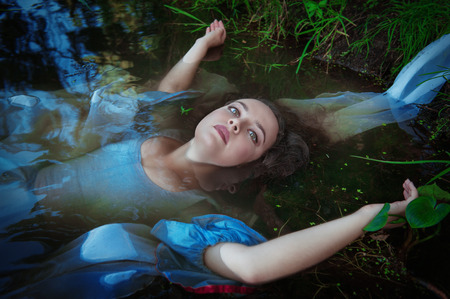 Young beautiful drowned woman in blue dress lying in the water outdoor
