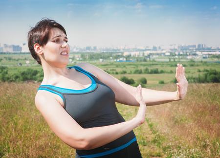 renounce: Beautiful plus size woman in sportswear making refuse gesture outdoor