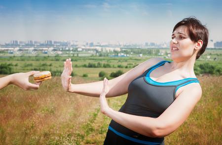 disinclination: Beautiful plus size woman in sportswear refusing junk food outdoor
