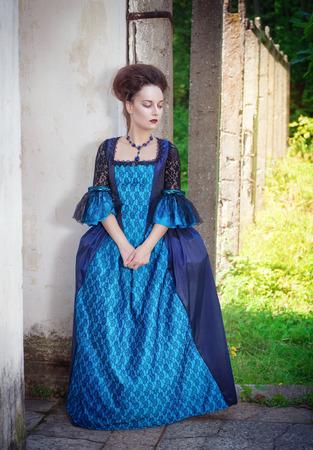 medieval dress: Joven y bella mujer en vestido medieval azul al aire libre