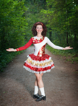 irish woman: Young woman in irish dance dress and wig welcoming outdoor Stock Photo