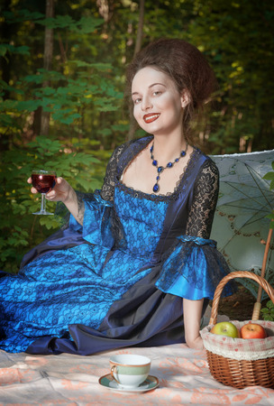 medieval dress: Young beautiful women in long medieval dress having picnic outdoor