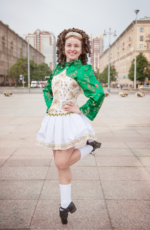 irish woman: Young woman in irish dance dress and wig dancing outdoor