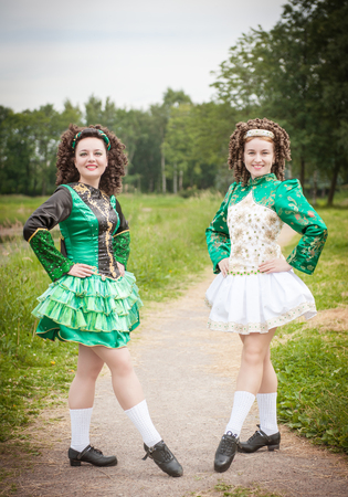 irish woman: Two young beautiful girl in irish dance dress and wig posing outdoor