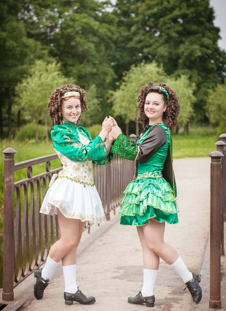 irish culture: Two young beautiful girl in irish dance dress and wig posing outdoor