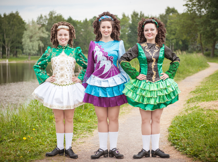 irish woman: Three young beautiful girls in irish dance dress and wig posing outdoor
