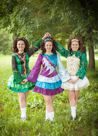 Three young beautiful girls in irish dance dress and wig posing outdoor photo