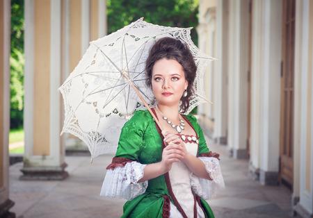 medieval dress: Joven y bella mujer en traje medieval verde con paraguas al aire libre