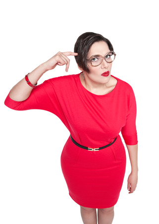stupid body: Beautiful plus size woman gesturing finger against her temple isolated