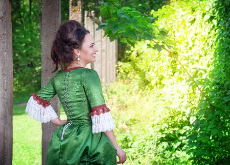 vestido medieval: Joven y bella mujer en vestido medieval verde al aire libre Foto de archivo