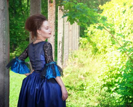 vestido medieval: Joven y bella mujer en vestido medieval azul al aire libre