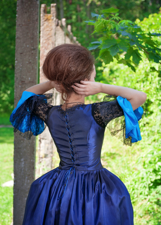 ruche: Beautiful young woman in blue medieval dress outdoor, back