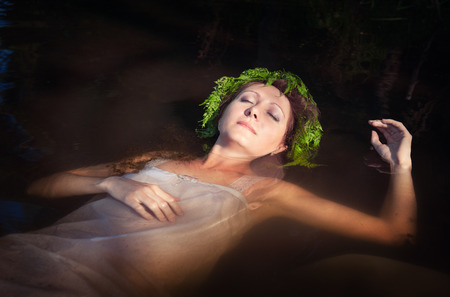 Young beautiful drowned woman with fern wreath lying in the water outdoor photo