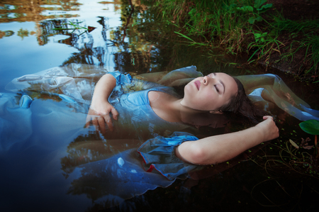 Young beautiful drowned woman in blue dress lying in the water outdoor photo