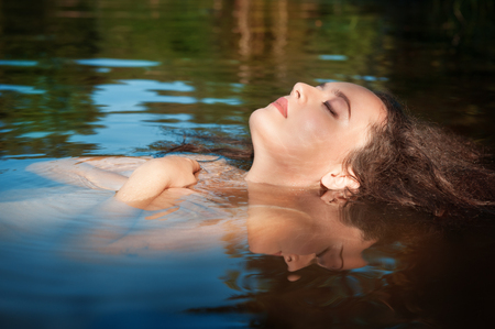 adult mermaid: Beautiful young woman lying in the water outdoor
