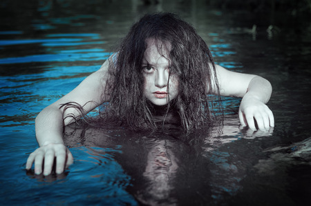 Young beautiful drowned ghost woman in the water outdoor photo