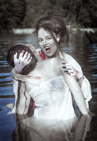 Beautiful vampire woman dressed white bloody shirt and her victim standing in the river photo