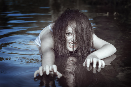 drowning: Young beautiful drowned ghost woman in the water outdoor