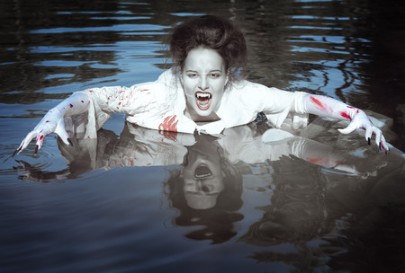 Beautiful vampire woman dressed white bloody shirt standing in the river photo