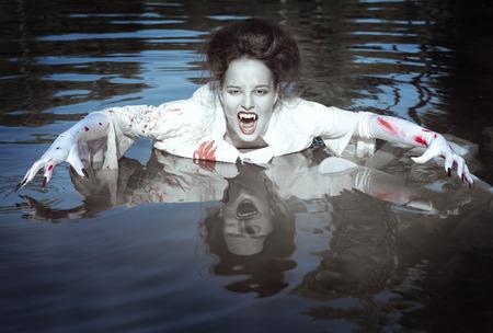 vampire teeth: Beautiful vampire woman dressed white bloody shirt standing in the river Stock Photo
