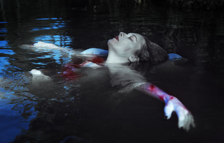 underwater scene: Young beautiful drowned woman in bloody dress lying in the water outdoor