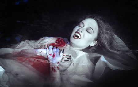 Beautiful vampire woman dressed white bloody shirt lying in the river Stock Photo