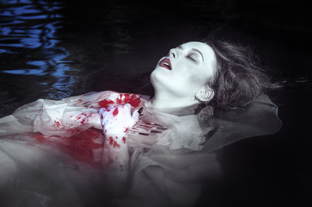 Young beautiful drowned woman in bloody dress lying in the water outdoor