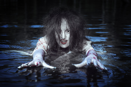 Beautiful witch woman dressed white bloody shirt standing in the river