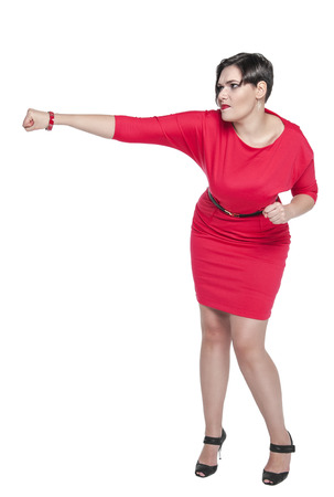 girl in red dress: Beautiful plus size woman in red dress beating something isolated on white background Stock Photo