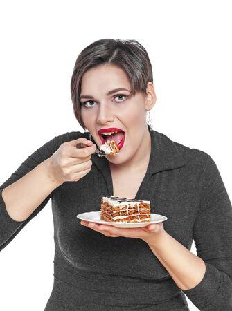 woman eating cake: Beautiful plus size woman eating cake isolated on white background Stock Photo