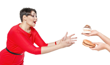 allurement: Beautiful plus size woman seduced with hamburger and pastry isolated