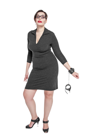 Beautiful plus size woman in black dress with handcuffs isolated on white background photo