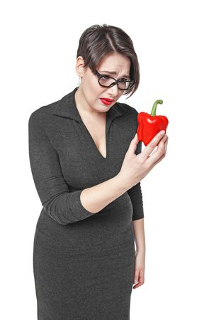 sadly: Plus size woman sadly looking on red pepper isolated on white background