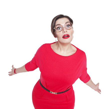 Surprised plus size woman in glasses shrugs her shoulders isolated photo