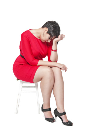 Sad plus size woman sitting on the chair isolated on white background