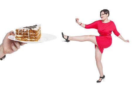 Mooie plus size vrouw afweren van ongezond voedsel op een witte achtergrond